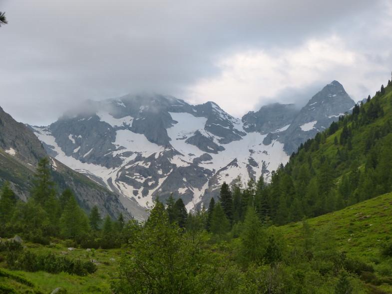 Der Gipfel in Wolken, die Kante etwas links der Bildmitte. Der Anstieg zum Einstieg erfolgt in der Rinne welche von der Bildmitte nach rechts oben zieht. An der Engstelle verlässt man diese und steigt mittig weiter auf.