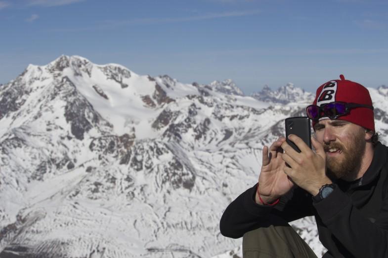 Sepp Unterwurzacher beim Handy spielen, dahinter die Ötztaler Wildspitze